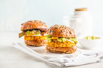 Vegan sweet potato (or pumpkin) burgers on white background. Vegetable burgers, avocado, vegetables and buns.