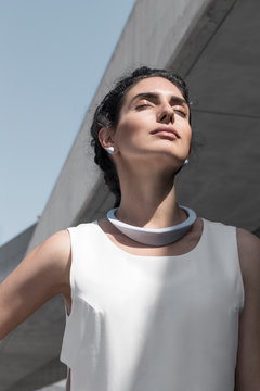 Beautiful woman with minimalist jewelry and outfit under the sun in concrete architecture site