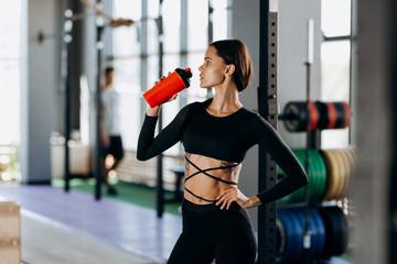 Slim dark-haired girl dressed in black sportswear drinks water in the gym near the sport equipment