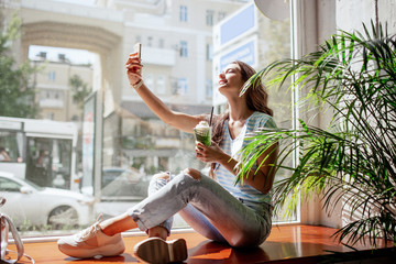 A young pretty girl with long hair,dressed in casual clothes,sits on a windowsill and takes a selfie with a cup of coffee in a modern cafe.