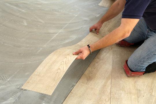 Work on laying flooring. Worker installing new vinyl tile floor.