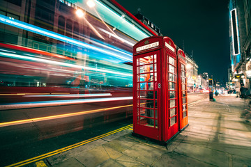 Fond de hotte en verre imprimé Londres bus rouge Light trails of a double decker bus next to the iconic telephone booth in London