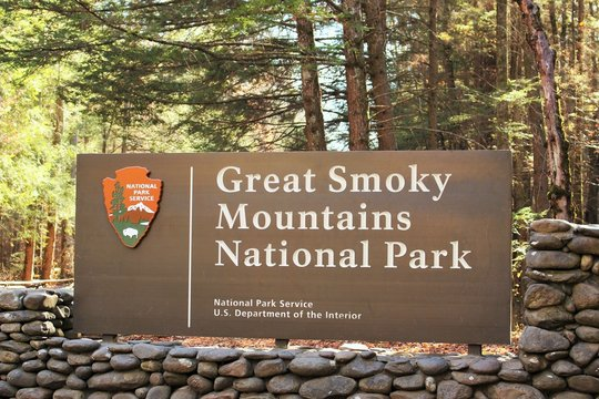 Daytime photo of a Great Smoky Mountains National Park entrance sign with stone surrounding and trees and sunshine in the background