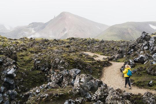 Woman in yellow raincoat walking through the lava field in Landmannalaugar national park, Iceland