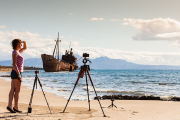 Woman with camera on tripod and shipwreck