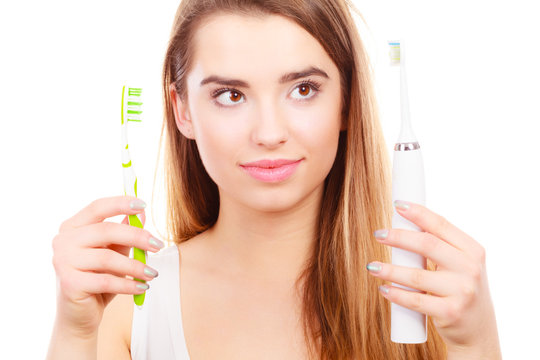 Woman with braces holding electric and traditional toothbrush