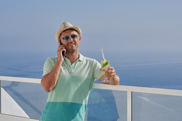 Happy man in sun hat talking on mobile phone and looking at sea from ... 4d42b961ae9c
