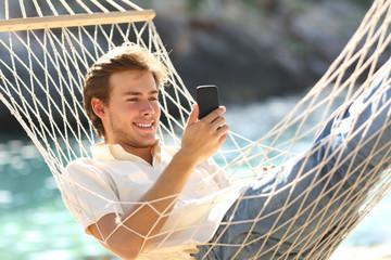 Happy man resting on a hammock using a smart phone