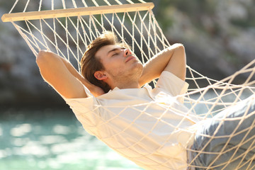 Relaxed man resting on a hammock on beach holiday