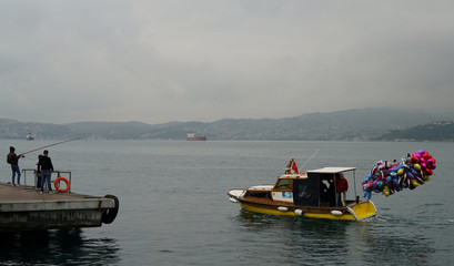 A man selling baloons sails on small boat in the Bosphorus in Istanbul