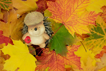 niedliche Zierfigur eines Igels sitzt in einem Blätterhaufen.