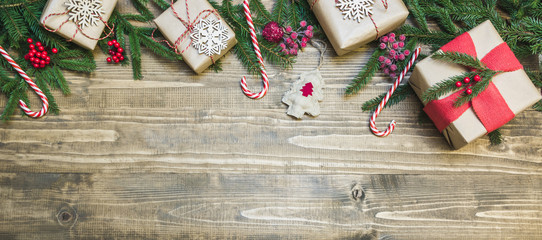 Christmas holiday banner - gifts, holly berries and decoration on wooden board. Holiday card. Top view.
