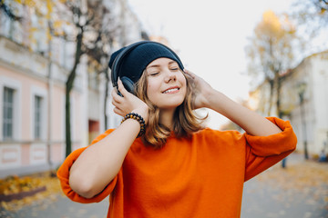 Young pretty hipster teen girl in black hat listening music via headphones on the autumn street