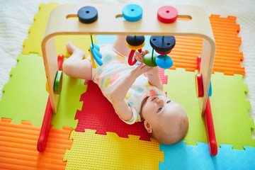 Smiling baby girl lying on play mat