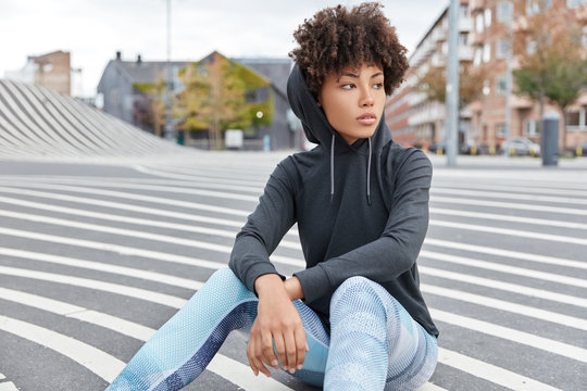Carefree ethnic young woman wears casual sweatshirt with hood, leggings sits on road against urban background, focused into distance, thinks about favourite sport. People and recreation concept