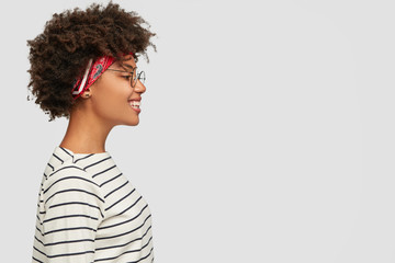 Profile of happy dark skinned girl wears striped clothes, headband, spectacles, smiles positively, isolated over white background for advertisement, promotion or slogan. Black woman stands sideways