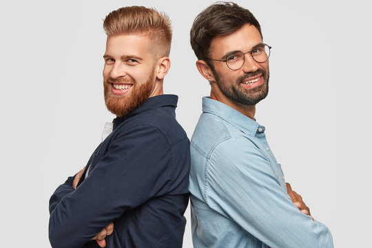 Best friend stand back to back, have friendly relationships, keep hands folded, smile gladfully, work as team, isolated over white background. Happy foxy bearded man and his partner pose indoor
