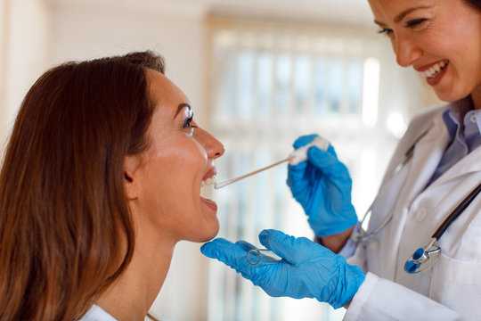 Young woman doctor takes a swab from the throat