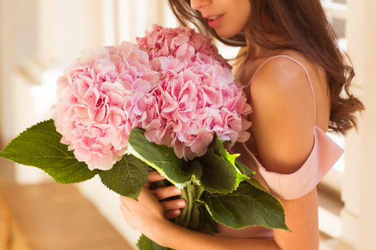 Beautiful woman holding a pink hydrangeas in her arms.