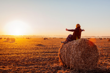 Happy middle-aged woman sitting on haystack in autumn field and feeling free with arms opened