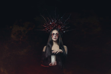 Terrible Halloween Vampire Woman portrait. Beauty Vampire Witch lady with blood on mouth posing in deep forest. Fashion Art design. holds a candle in his hands and reads curses