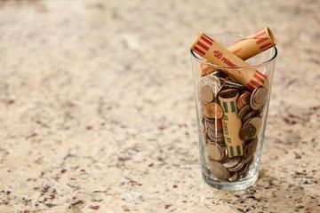 Glass jar of coins in cup on countertop desk money savings debt bank rich poor dollar finance wealth change market cash