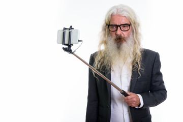 Studio shot of senior bearded businessman taking selfie picture