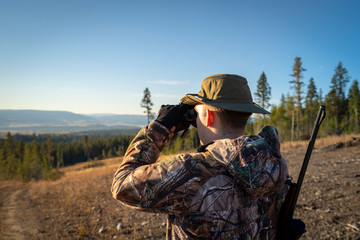 A Hunter Glassing with Binoculars at a Beautiful Landscape Wall mural