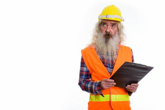 Studio shot of senior bearded man construction worker holding cl