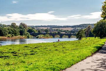 A man running along a shore of river Dee in nice sunny day, Aberdeen, Scotland
