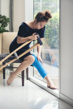 injury woman with leg splint sitting and wooden crutches at hospital