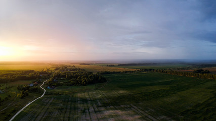 Great panorama of the countryside from the height of the quadrocopterf during sunset and rain in the distance