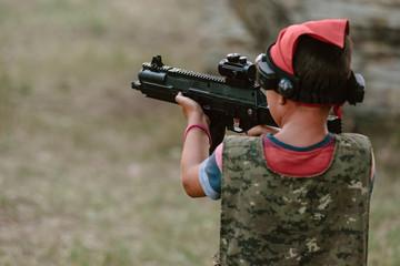 Young boy playing lasertag and aiming optical gun