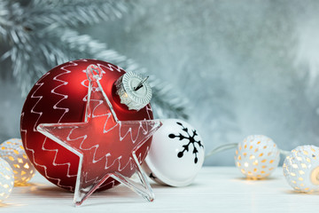 red christmas ball, garlands and decorative glass star on defocused grey background with fir tree branch