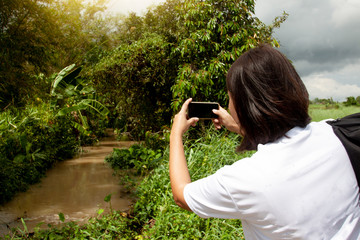 Asia women take photo by smartphone to Landscape of river countryside.