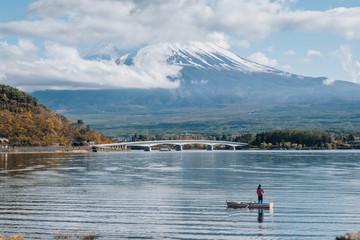 Mount fuji san at Lake kawaguchiko in japan on sunrise. people on boat are fishing in the lake