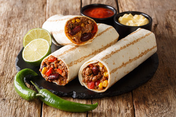 Traditional grilled burritos with beef and vegetables served with sauces close-up. horizontal