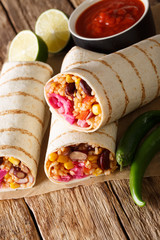 Mexican grilled veggie burrito with rice and vegetables served with tomato sauce closeup. vertical