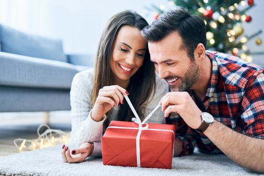 Happy couple opening a Christmas present