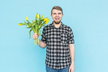 Man with bouquet of yellow tulips. Yellow tulips in the hands of a bearded man on blue background