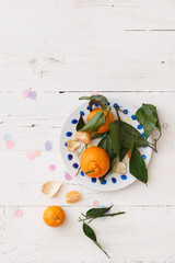 Closeup of plate with tangerines on white wooden background with colorful confetti. After party