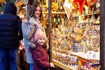 Young mother and cute little daughter selecting decoration on Christmas market. Beautiful woman and adorable kid girl shopping for toys and decorative houses. Xmas market in Germany.