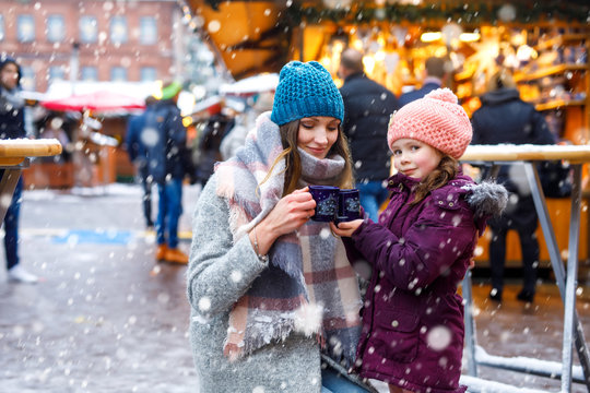 Happy kid girl and young beautiful woman with cup of steaming hot chocolate and mulled wine. Adorable child and beautiful mum on Christmas market in Germany. Family walking on Xmas market.