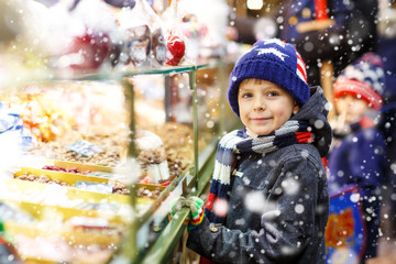 Little cute kid boy near sweet stand with gingerbread and nuts. Happy child on Christmas market in Germany. Traditional leisure for families on xmas. Holiday, celebration, tradition, childhood