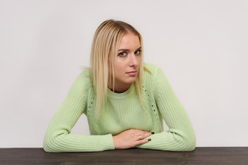 Photo portrait of a beautiful blonde girl talking on a white background sitting at the table.