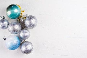 Nice christmas balls in silver and blue colors on  white texture surface. Top view.