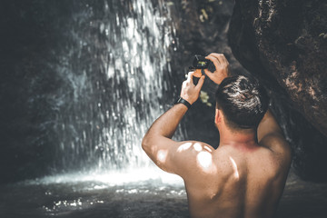 Tourist man on a waterfall background holds an action camera and takes a picture. Bali island.