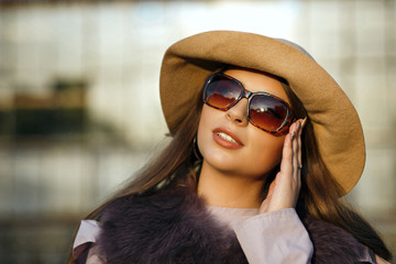 Elegant brunette tanned model with natural makeup wearing hat, sunglasses and fur coat. Empty space