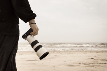 Man walking on beach with camera