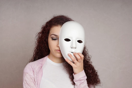 sad depressed young woman hiding her face behind mask
